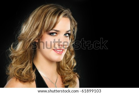 Portrait of a pretty young woman with long blond hair photoraphed on dark barkground - stock photo