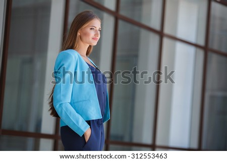 Portrait of a professional business woman smiling outside in the city with buildings in the background. Portrait of business woman outdoor.  - stock photo