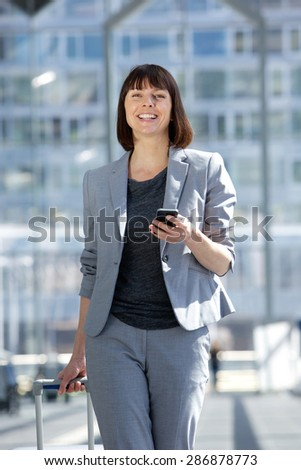 Portrait of a professional business woman traveling with bag and mobile phone - stock photo