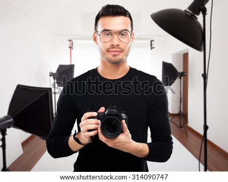 Portrait of a professional photographer in his studio - stock photo