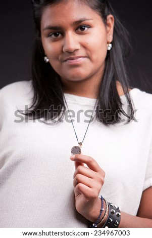 portrait of a proud indian girl showing a local coin (rupee) - stock photo