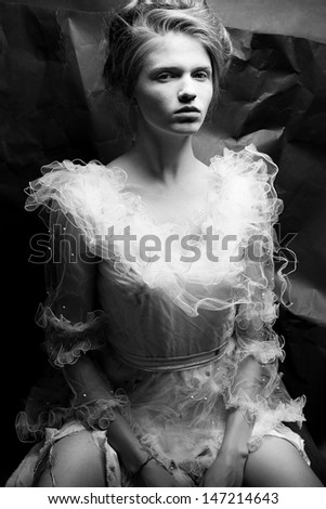 Portrait of a queen like young woman in white trashy dress posing over wrinkled black paper background. Vintage (retro, classic) style. Black and white (monochrome) studio shot - stock photo