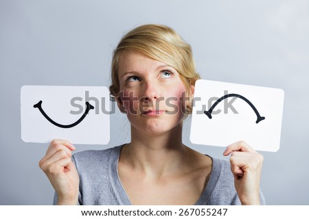 Portrait of a Questioning Woman Holding Happy and Unhappy Survey Mood Board - stock photo