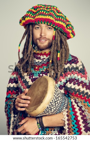 Portrait of a rastafarian guy playing his drum. - stock photo