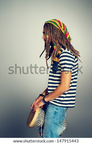 Portrait of a rastafarian young man playing his drum. - stock photo