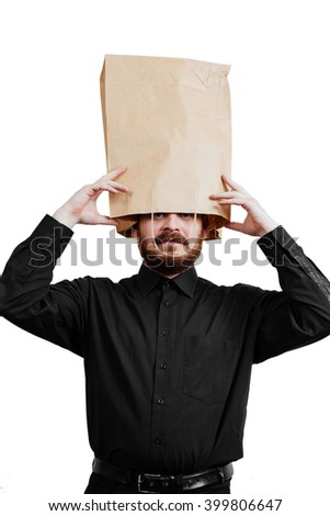 Portrait of a red-bearded, balding male brutal. White isolated background. Black shirt and pants. Paper bag over head. looks out of the package - stock photo