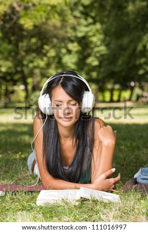 Portrait of a relaxed beautiful young student girl relaxing, studying, having fun outdoors. - stock photo