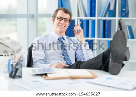 Portrait of a relaxed businessman with legs on the table smiling and looking at camera on the foreground - stock photo