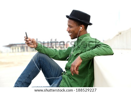 Portrait of a relaxed man listening to music on mp3 player outdoors - stock photo