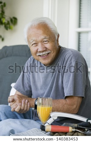 Portrait of a relaxed smiling senior man with orange juice - stock photo