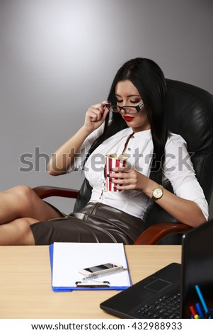 Portrait of a relaxed young businesswoman sitting with legs on desk - stock photo