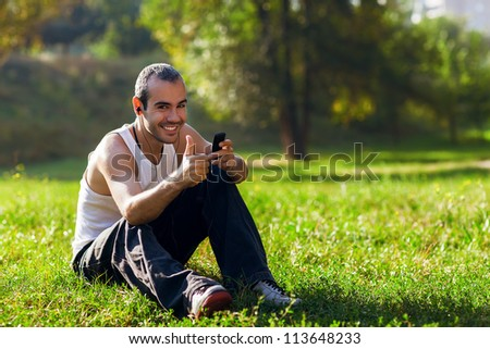 Portrait of a relaxed young man sitting on grass in park and listening to music on headphone - stock photo