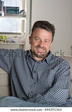 Portrait of a relaxed young man sitting on sofa in the house - stock photo