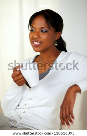 Portrait of a relaxed young woman holding a white mug while sitting pensive on couch at home indoor - stock photo