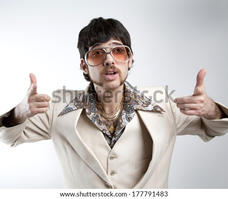 Portrait of a retro man in a 1970s leisure suit and sunglasses pointing to the camera  - stock photo