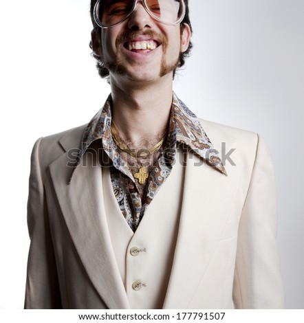 Portrait of a retro man with a gold tooth in a 1970s leisure suit and sunglasses smiling to the camera  - stock photo