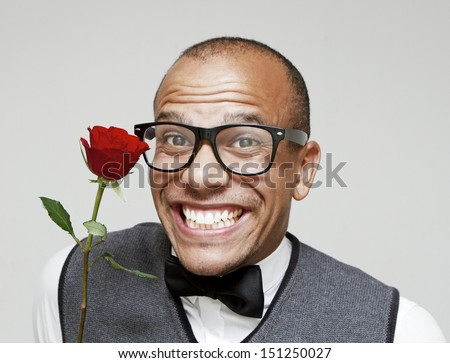 Portrait of a Romantic Geeky Valentine date. Geek in love holding a rose excitedly - stock photo