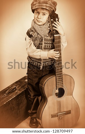 Portrait of a romantic little boy standing  with his guitar. Retro style. - stock photo