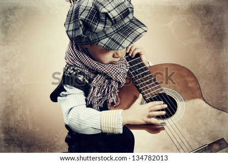 Portrait of a romantic little boy with his guitar. Retro style. - stock photo