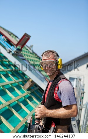 Portrait of a roofer using safety goggles, ear mufflers and holding a hand circular saw - stock photo
