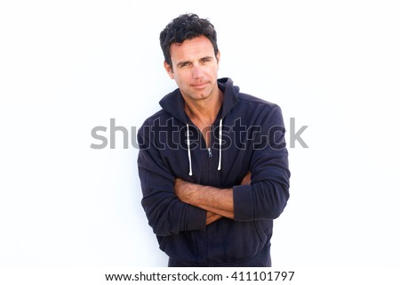 Portrait of a rugged handsome middle aged man standing with arms crossed against white background - stock photo