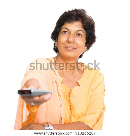 Portrait of a 50s Indian mature woman watching tv and hand holding remote control changing channel, isolated on white background. - stock photo