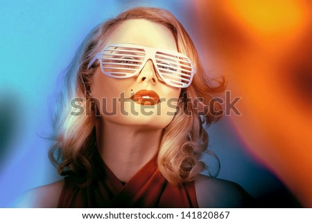 Portrait of a 1950s style Pin-up fashion girl in retro american sunglasses posing in front of a colorful background. Stylish women - stock photo