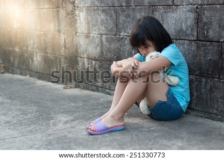 portrait of a sad and lonely Asian girl against grunge wall background - stock photo