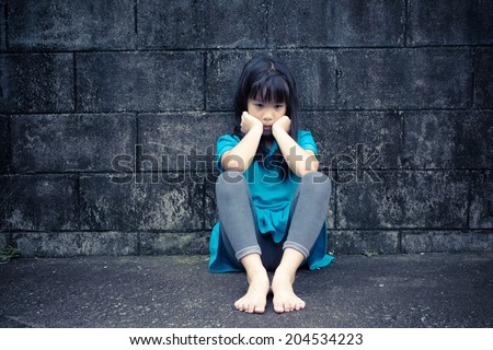 portrait of a sad Asian girl against grunge wall background - stock photo