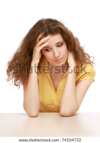Portrait of a sad beautiful woman sitting at the table - stock photo