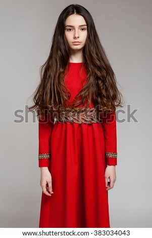 Portrait of a sad brunette girl with long hair in a red dress, gray background - stock photo