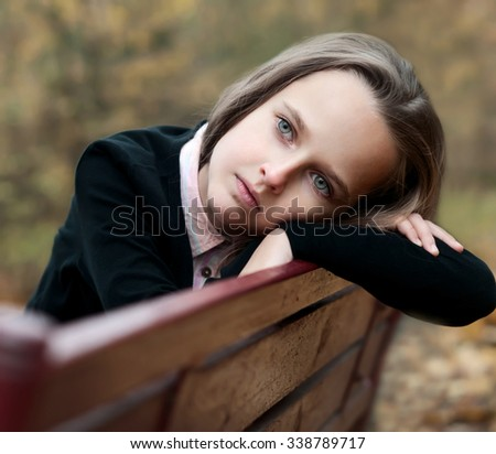 Portrait of a sad girl in the autumn park - stock photo
