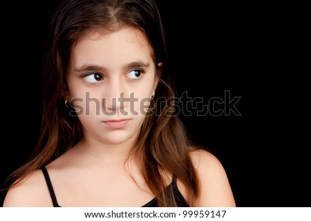 Portrait of a sad hispanic girl with tears on her face isolated on black - stock photo