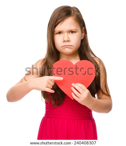 Portrait of a sad little girl holding red heart and pointing to it using index finger, isolated over white - stock photo