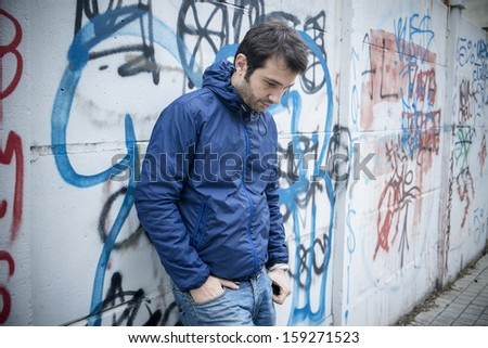 portrait of a sad man in a urban street - stock photo