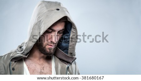 Portrait of a sad man with beard and a hood - stock photo