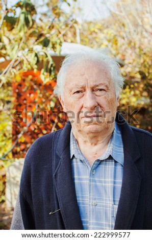 Portrait of a sad senior man in autumn park - stock photo