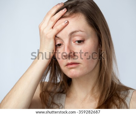 Portrait of a sad woman in a beige shirt, one hand on the forehead, isolated on cold white background. Close up - stock photo
