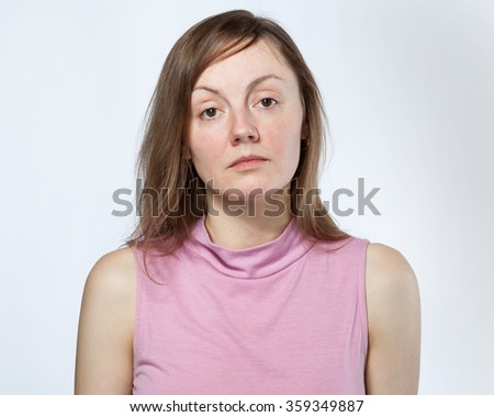 Portrait of a sad woman in a pink shirt on white background - stock photo