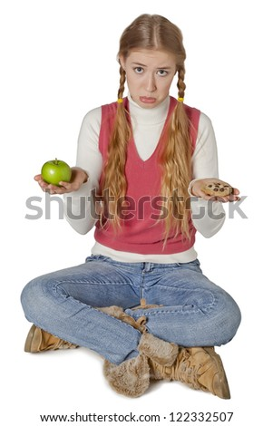 Portrait of a sad woman thinking what to eat between apple and cookie - stock photo