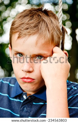 Portrait of a sad young boy sitting on a sling in the garden - stock photo