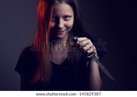 Portrait of a scary demonic teen girl with a knife - stock photo