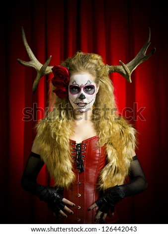 Portrait of a scary woman wearing sugar skull and thorns with hands on