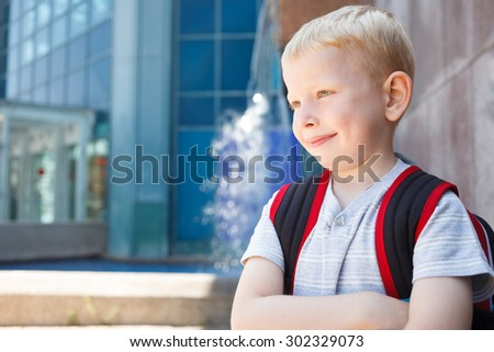 Portrait of a school boy standing in front of school - stock photo
