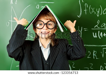 Portrait of a schoolboy in big round spectacles with a book at a classroom. - stock photo