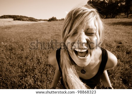 portrait of a screaming young woman outdoors in summer - stock photo