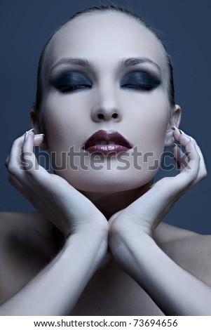 Portrait of a seductive glamorous lady on blue background - stock photo