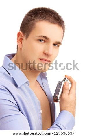 Portrait of a seductive young man spraying perfume - stock photo