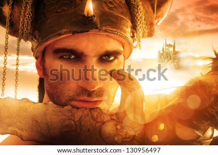 Portrait of a seexy strong warrior holding sword in golden light with fantasy background - stock photo