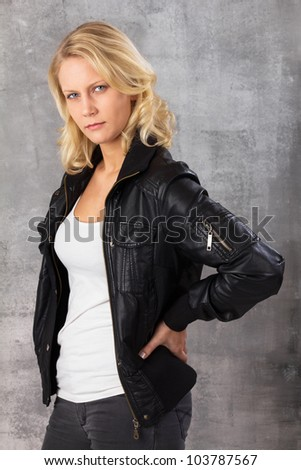 Portrait of a self-confident modern woman with hands on hips looking at the camera. Studio shot against a gray background. - stock photo
